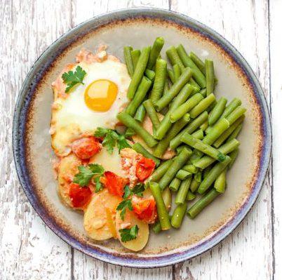 Aardappelschotel met sperziebonen en ontbijtspek
