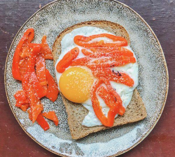 Gebakken ei op brood met geroosterde paprika