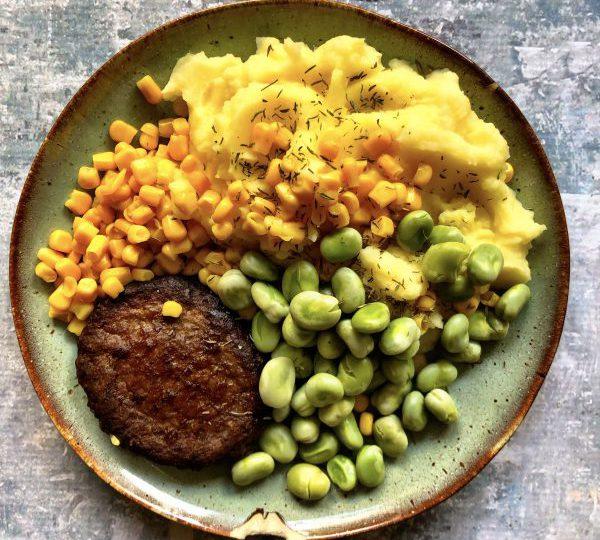 Aardappelpuree met tuinbonen, maïs en hamburger